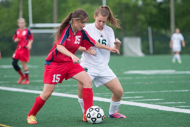 Father Gabriel Richard's Lilly Geppner and Hanover-Horton's Peter Roessing fight for the ball during the regional semifinal game Wednesday, May 29.